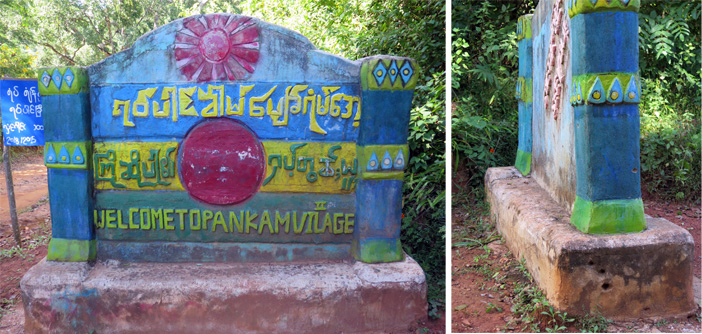 The colourful sign announcing Pankam Village had visible bullet pocks around the side and back